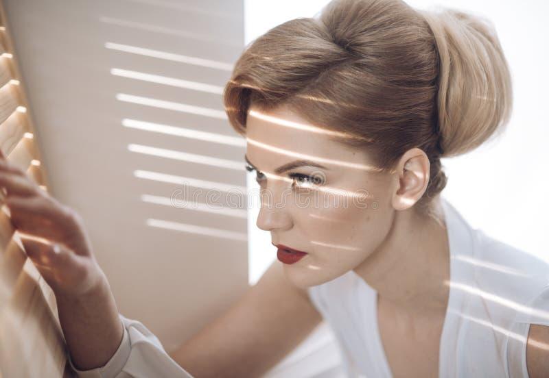 Mujer con la cara concentrada con miradas del maquillaje a través de la persiana, espiando foto de archivo libre de regalías