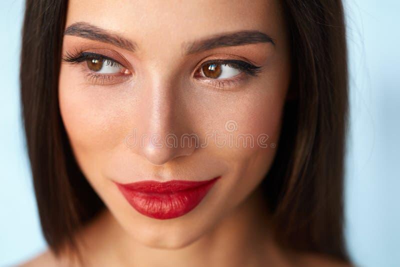 Mujer con la cara de la belleza y los labios rojos hermosos del maquillaje y atractivos foto de archivo