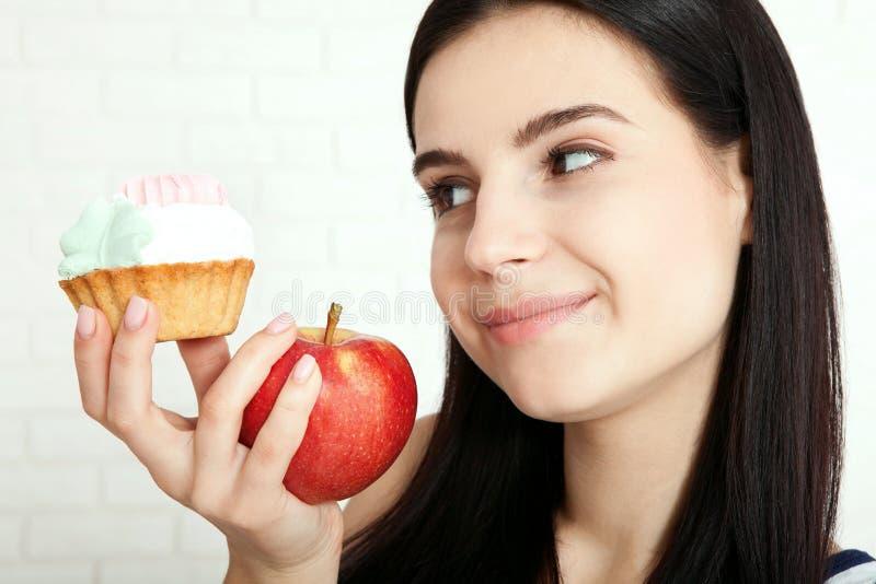 Mujer con la cara del primer de la manzana Las mujeres hermosas existen para limpiar la piel en la cara que elige comer una manza fotografía de archivo