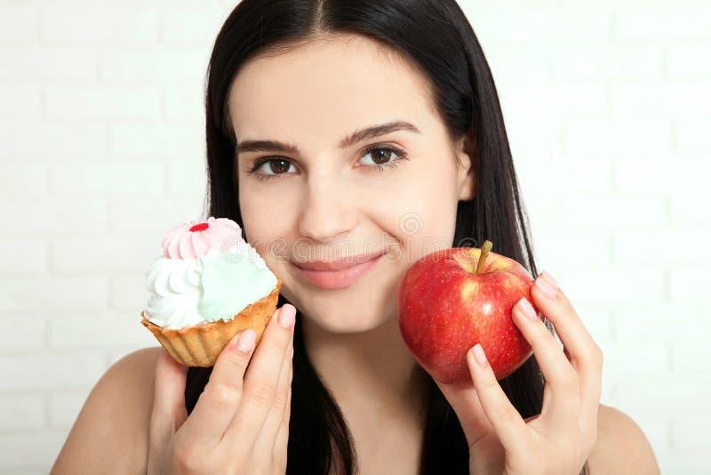 Mujer con la cara del primer de la manzana Las mujeres hermosas existen para limpiar la piel en la cara que elige comer una manza fotografía de archivo libre de regalías