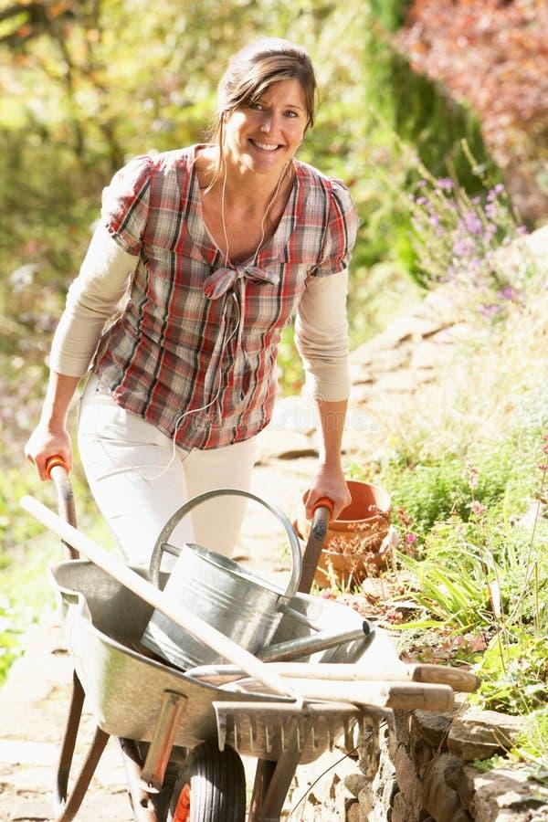 Mujer con la carretilla que trabaja al aire libre en jardín foto de archivo