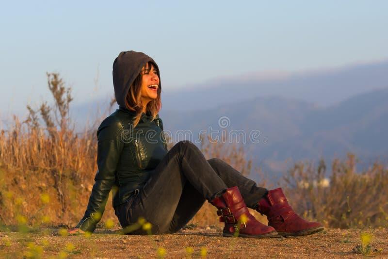 Mujer con la chaqueta y botas asentadas en la risa de tierra imagenes de archivo