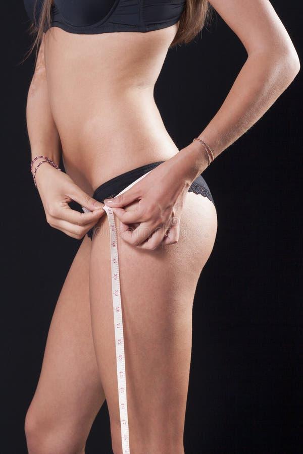 Mujer con la cicatriz en su brazo, midiendo su cintura imagen de archivo libre de regalías
