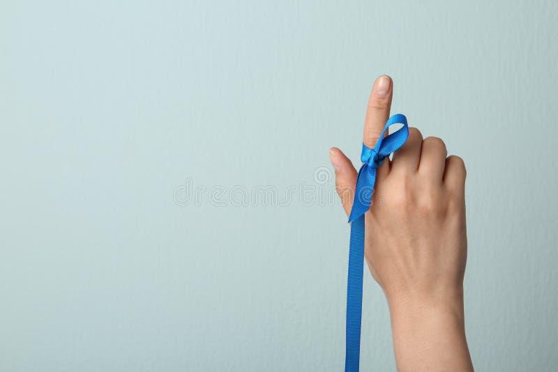 Mujer con la cinta azul en el finger contra fondo ligero Símbolo de problemas sociales y médicos imágenes de archivo libres de regalías