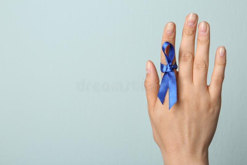 Mujer con la cinta azul encendido contra el fondo ligero, primer Símbolo de problemas sociales y médicos fotos de archivo