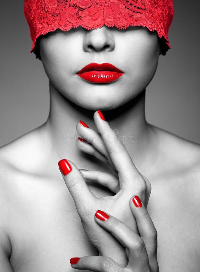 Mujer con la cinta de encaje roja en ojos fotos de archivo