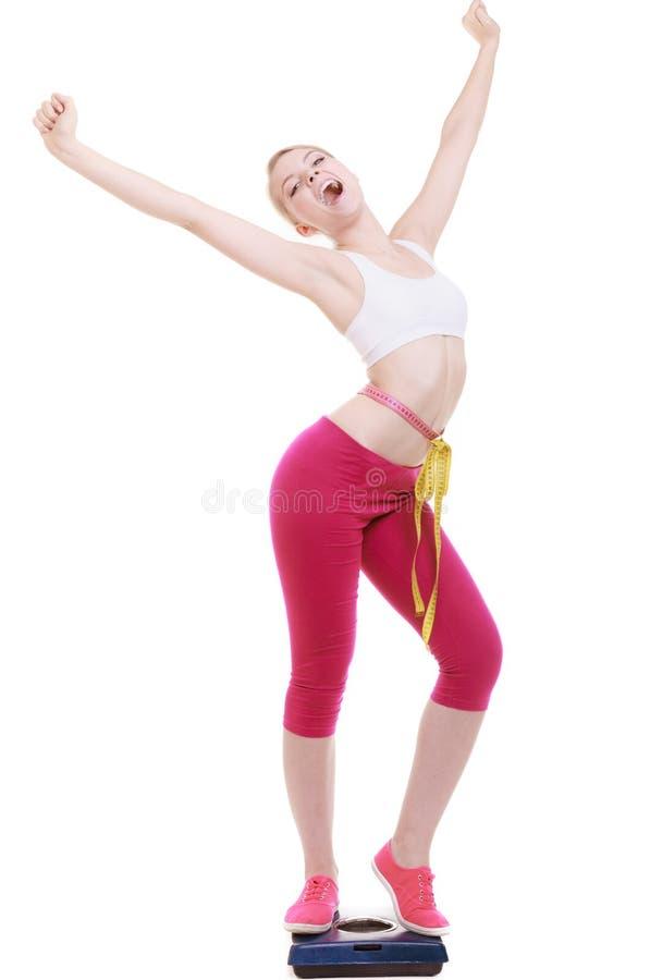 Mujer con la cinta de la medida en escala que celebra weightloss foto de archivo