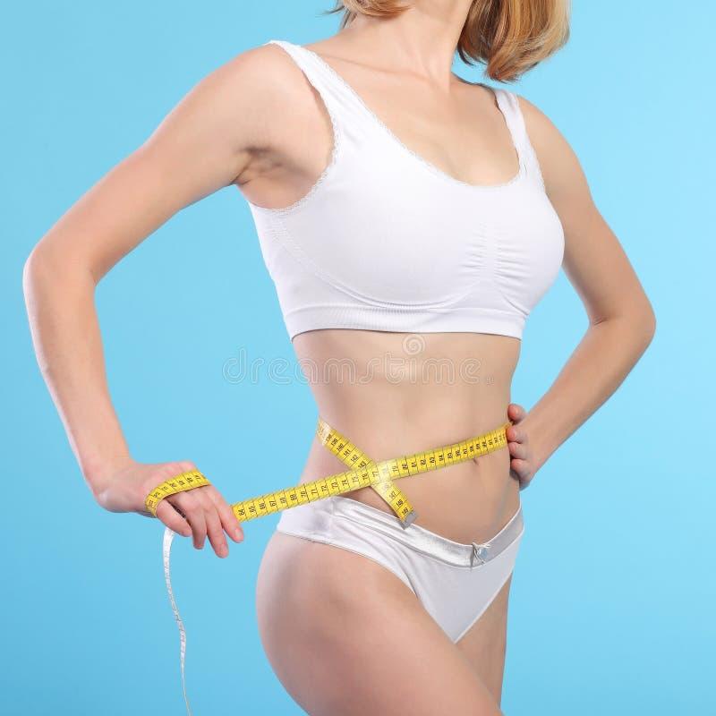 Mujer con la cinta de la medida sobre blanco imagenes de archivo