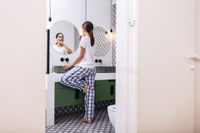 Mujer con la cola de caballo que lleva los pijamas holgados que cepillan los dientes fotos de archivo