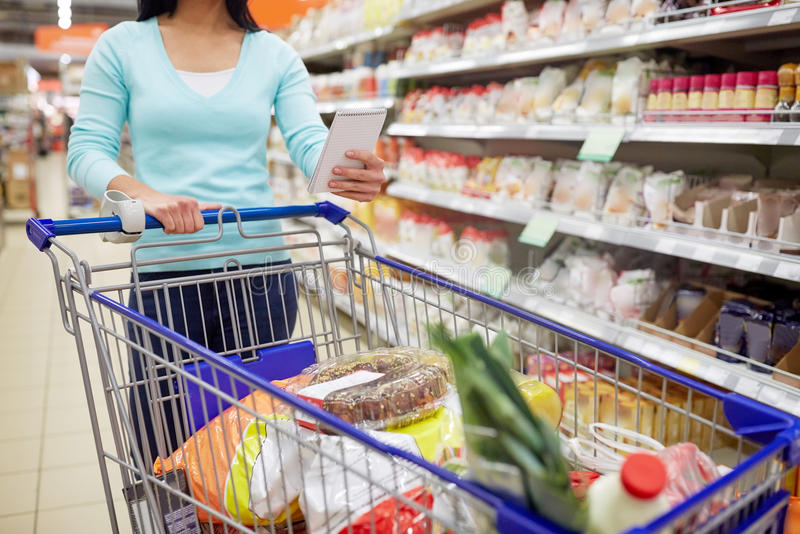Mujer con la comida en carro de la compra en el supermercado fotos de archivo