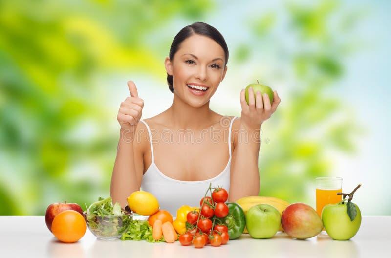 Mujer con la comida vegetal que muestra los pulgares para arriba fotografía de archivo libre de regalías
