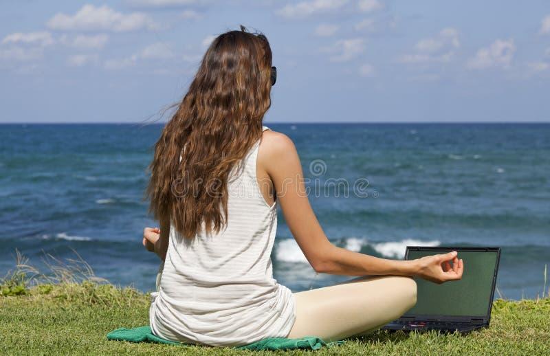 Mujer con la computadora portátil en actitud de la yoga fotografía de archivo libre de regalías