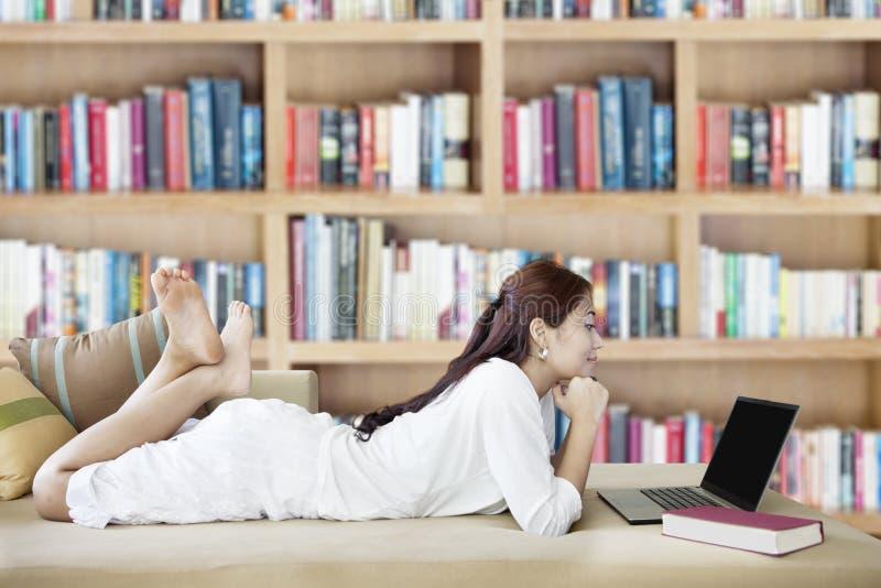 Mujer con la computadora portátil en biblioteca fotos de archivo libres de regalías