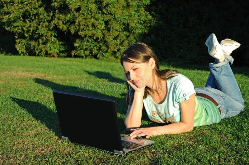 Mujer con la computadora portátil en césped imagenes de archivo