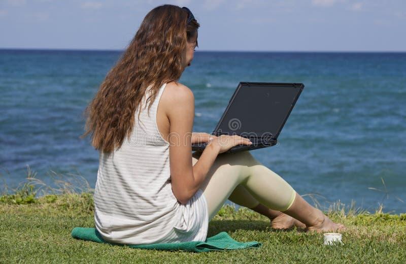 Mujer con la computadora portátil en la playa imagenes de archivo