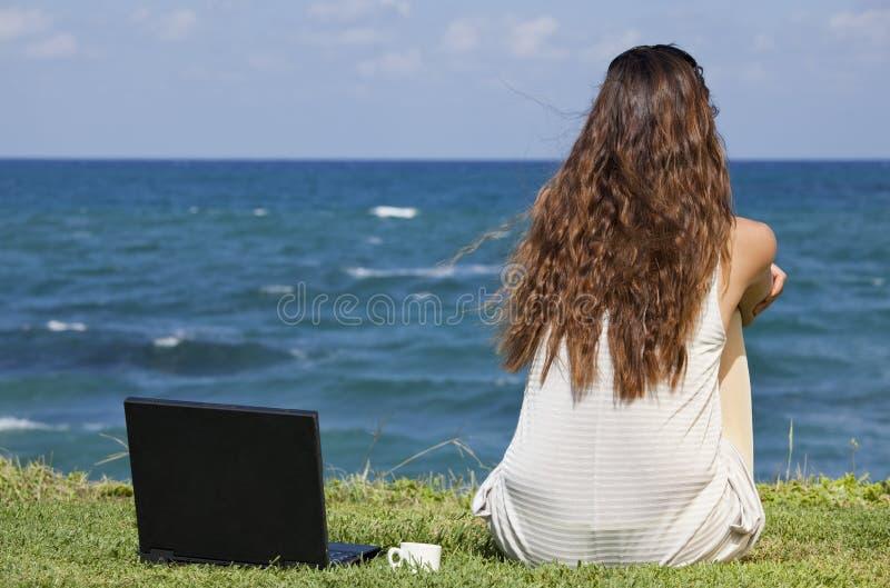 Mujer con la computadora portátil en la playa foto de archivo libre de regalías