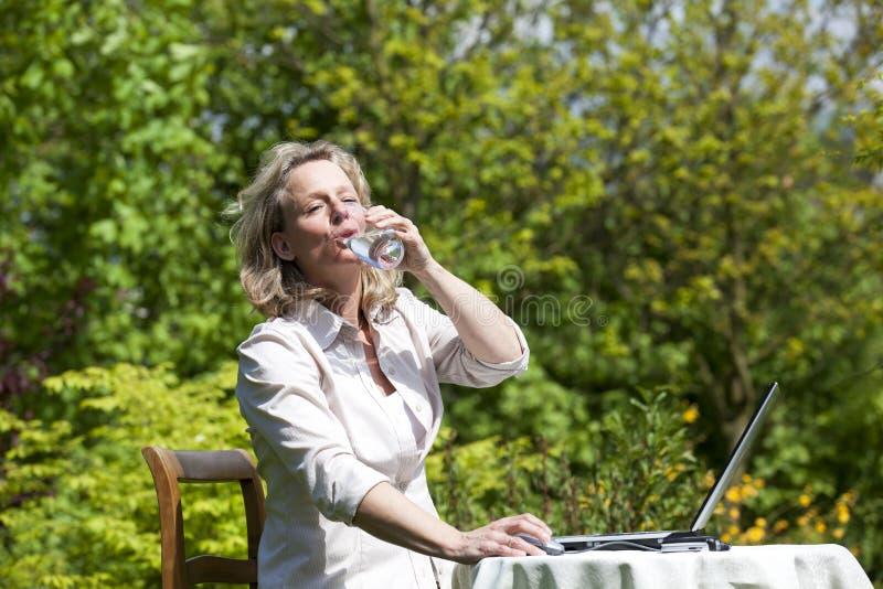 Mujer con la computadora portátil que bebe un vidrio de agua fotografía de archivo libre de regalías