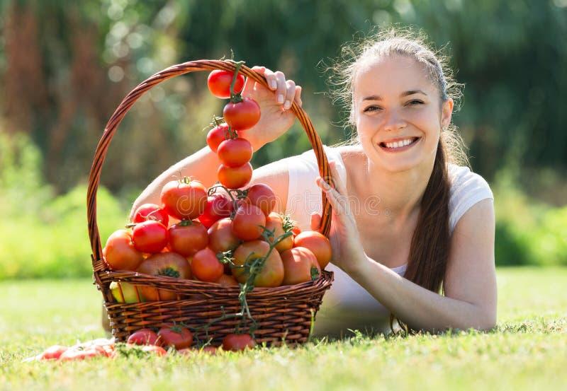 Mujer con la cosecha del tomate en jardín imagenes de archivo