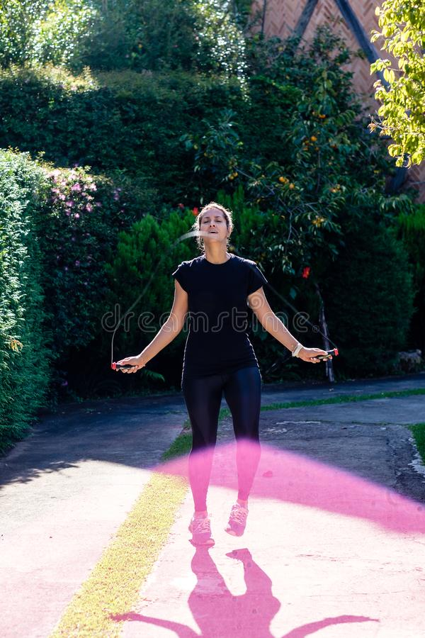 Mujer con la cuerda de salto negra de la ropa en el parque imágenes de archivo libres de regalías