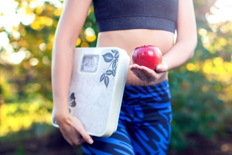 Mujer con la escala y la manzana roja al aire libre El adelgazar, dieta y healt foto de archivo