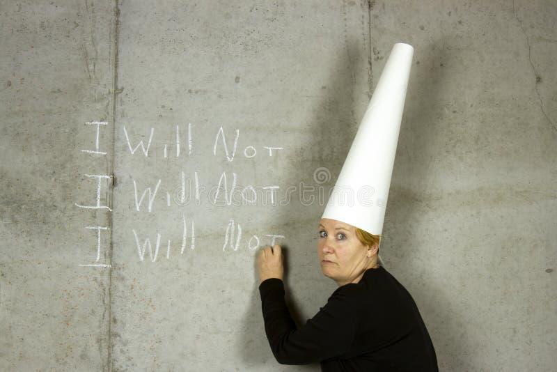 Mujer con la escritura del casquillo de tonto que NO foto de archivo