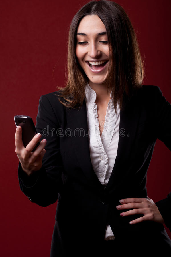 Mujer con la expresión alegre a su móvil fotografía de archivo