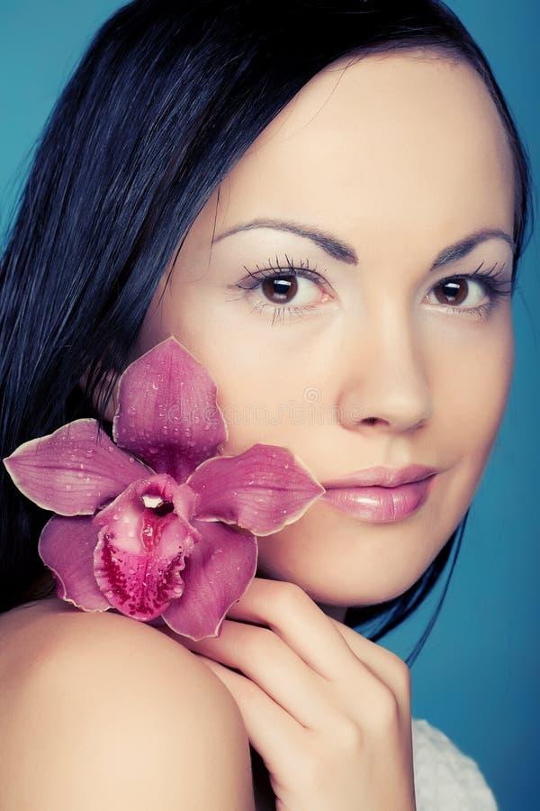 Mujer con la flor de la orquídea fotos de archivo