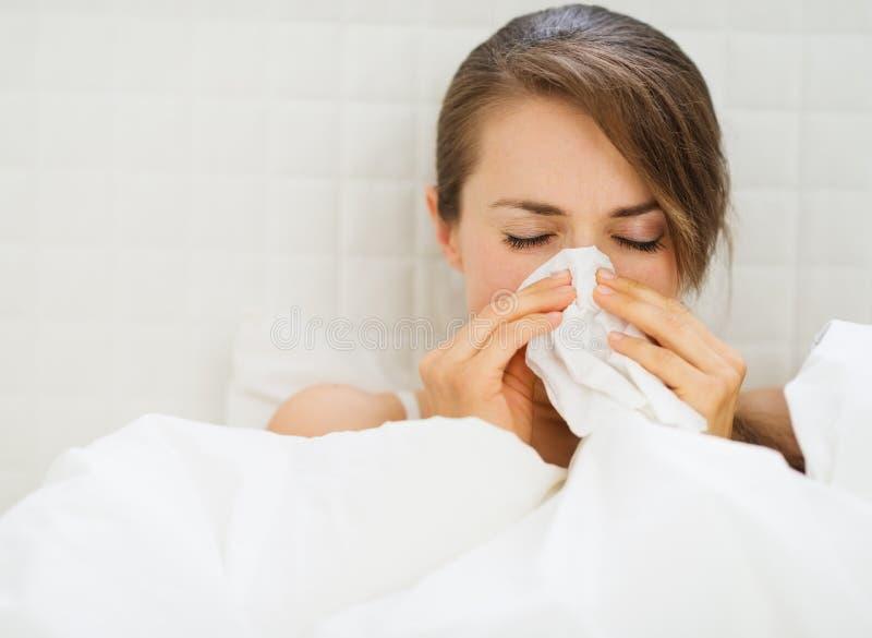 Mujer con la gripe que pone en cama foto de archivo libre de regalías