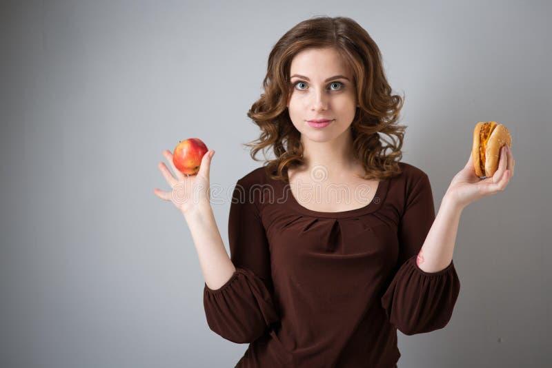 Mujer con la hamburguesa y la manzana fotos de archivo libres de regalías