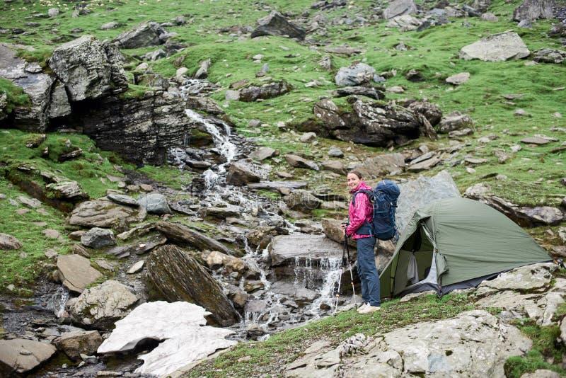 Mujer con la hermosa vista de la corriente de la montaña en las montañas de Fagaras fotos de archivo libres de regalías