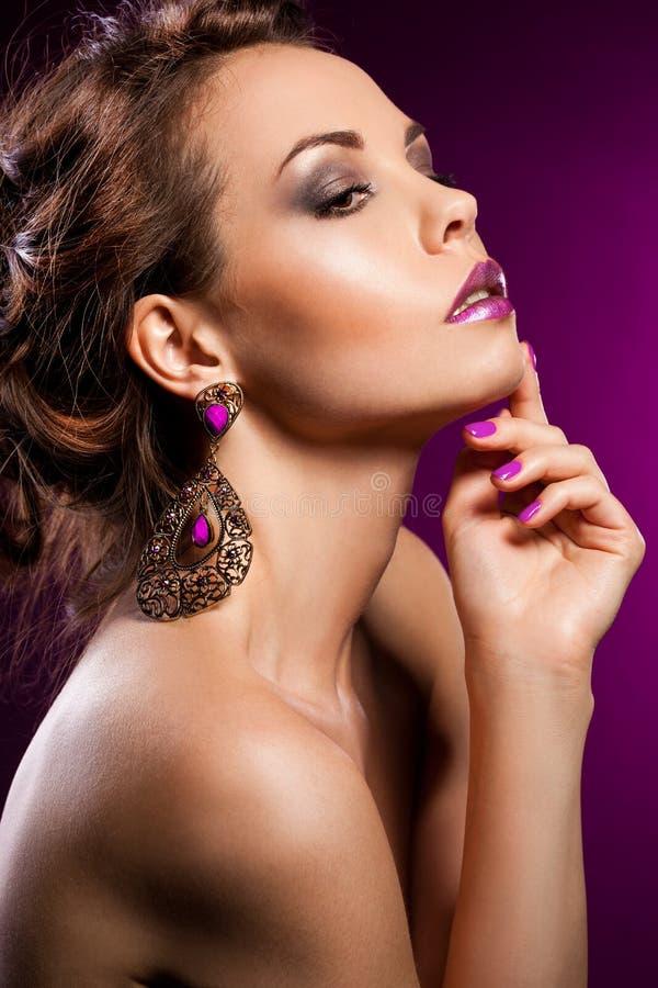 Mujer con la joyería violeta foto de archivo