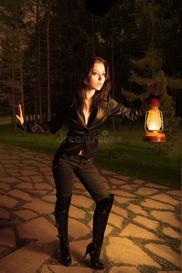 Mujer con la lámpara de petróleo en la noche imagen de archivo