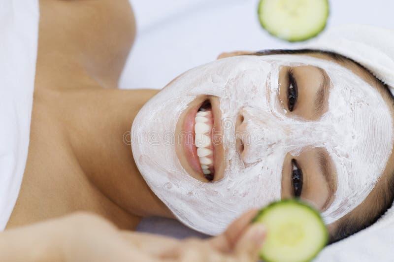 Mujer con la máscara facial que lleva a cabo rebanadas del pepino foto de archivo