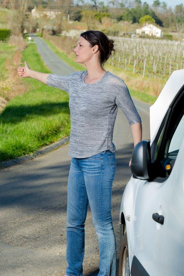 Mujer con la maleta que intenta parar el coche fotos de archivo libres de regalías