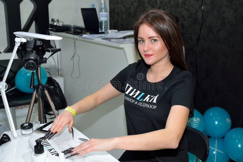 Mujer con la manicura del negro del diseñador en los ficheros de clavo del salón del lugar de trabajo imagen de archivo