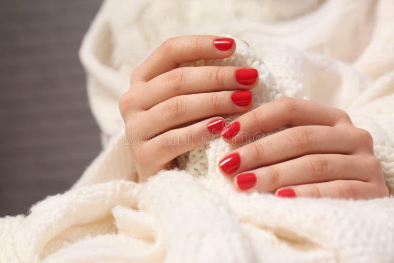 Mujer con la manicura roja que sostiene la tela hecha punto en fondo borroso Tendencias del esmalte de uñas fotografía de archivo