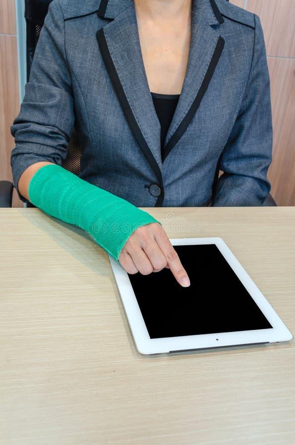 Mujer con la mano quebrada y el molde verde que trabajan en la tableta en oficina fotos de archivo