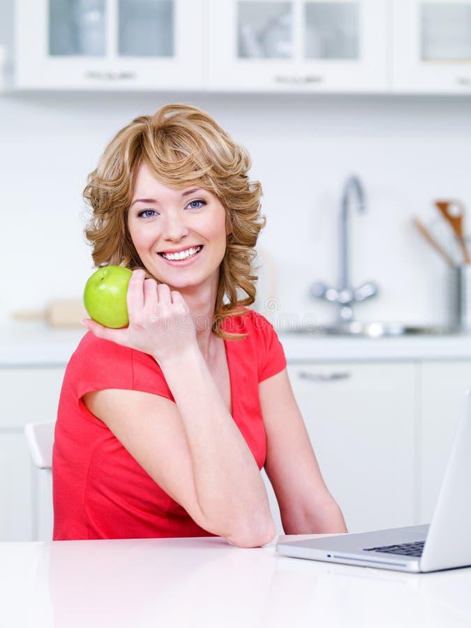 Mujer con la manzana verde en la cocina foto de archivo