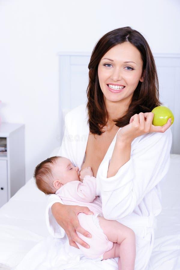 Mujer con la manzana verde que amamanta a su bebé imagen de archivo