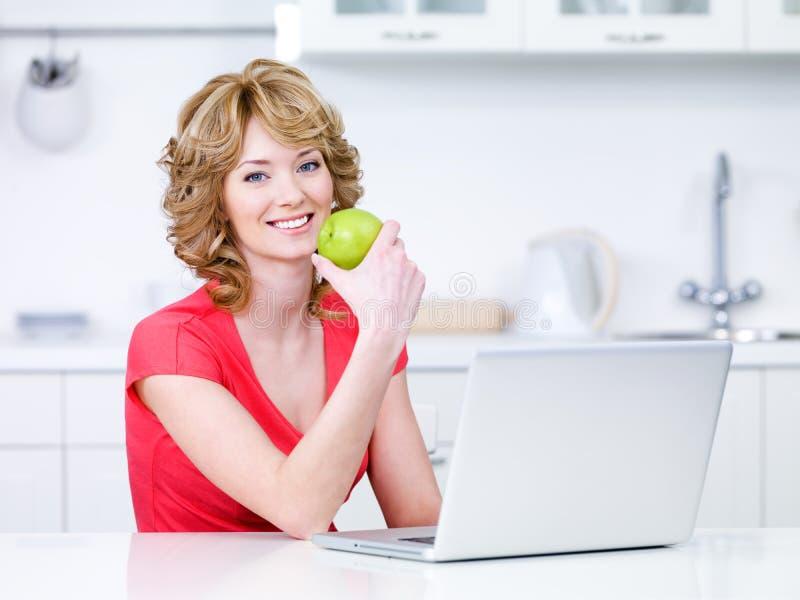 Mujer con la manzana y la computadora portátil verdes imagen de archivo