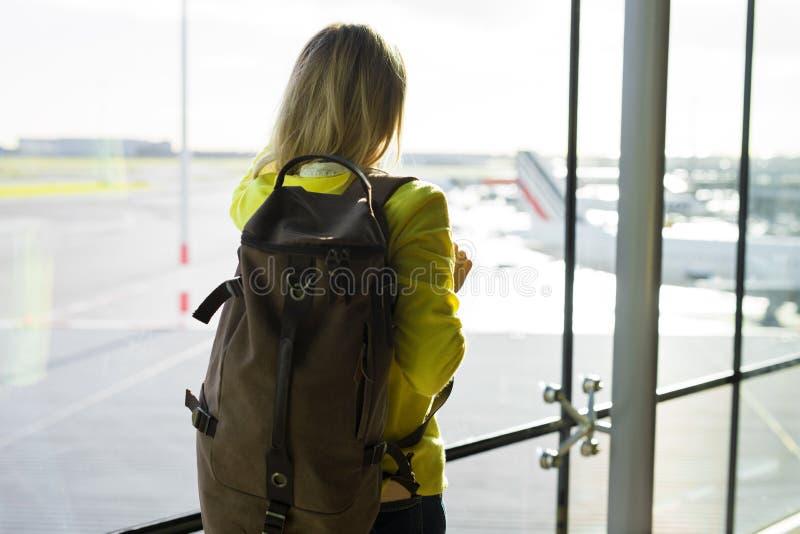 Mujer con la mochila que camina en aeropuerto foto de archivo libre de regalías