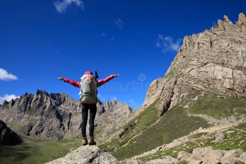 Mujer con la mochila que camina en concepto del éxito de la forma de vida del viaje de las montañas fotografía de archivo libre de regalías