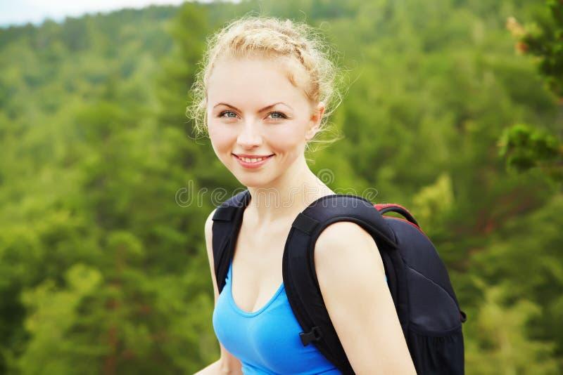 Mujer con la mochila que camina en las montañas imagen de archivo libre de regalías