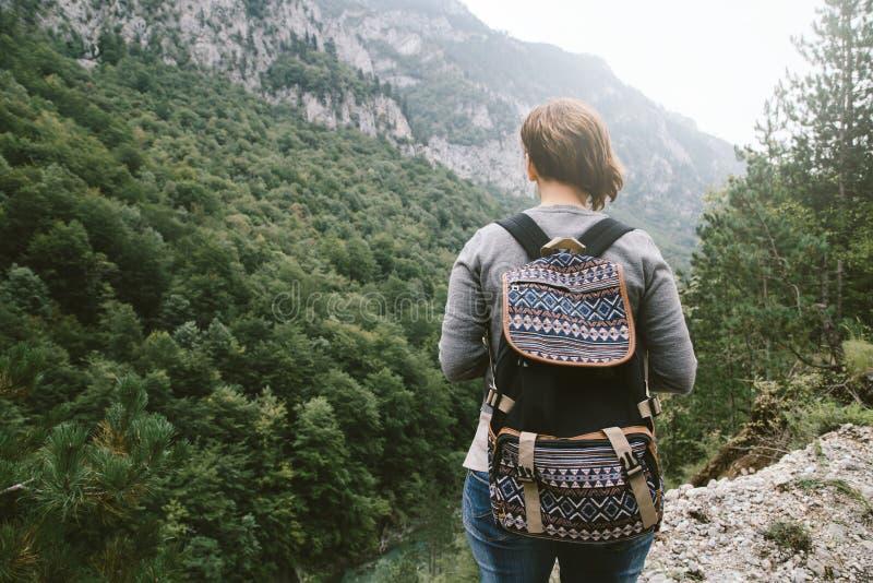 Mujer con la mochila que coloca las montañas cercanas imágenes de archivo libres de regalías