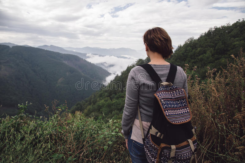Mujer con la mochila que coloca las montañas cercanas fotos de archivo