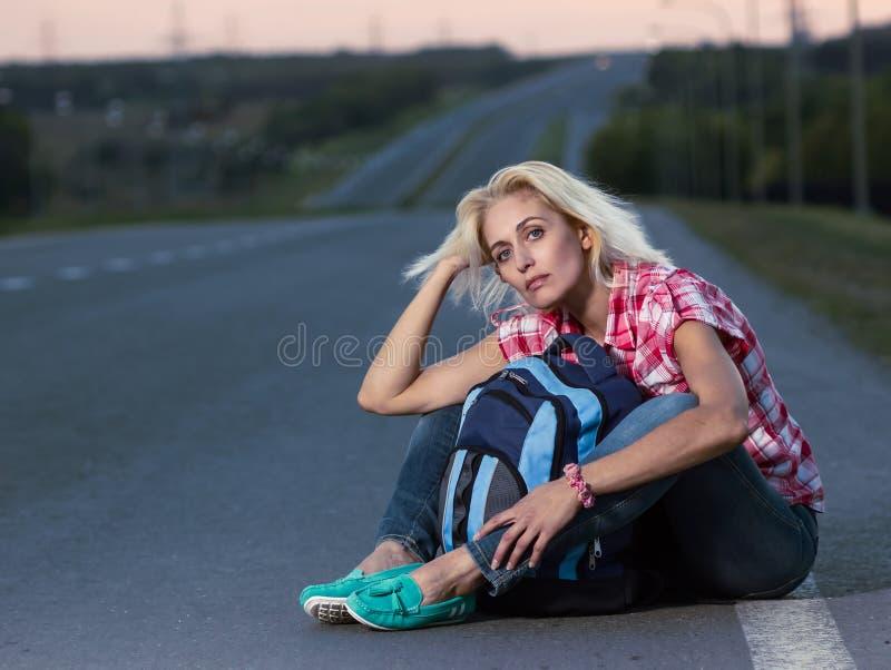 Mujer con la mochila que se sienta en el camino foto de archivo