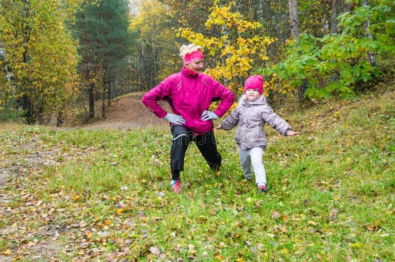 Mujer con la muchacha que hace aeróbicos en parque del otoño foto de archivo libre de regalías