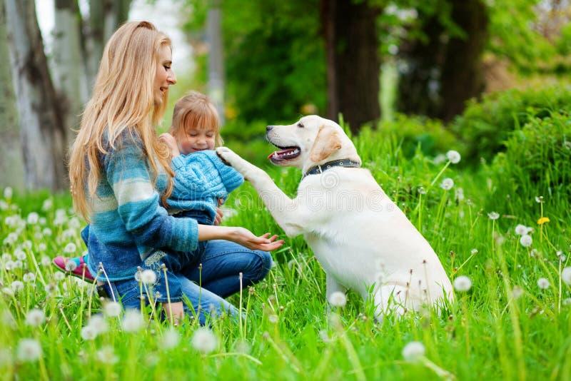 Mujer con la muchacha y el perro fotografía de archivo libre de regalías