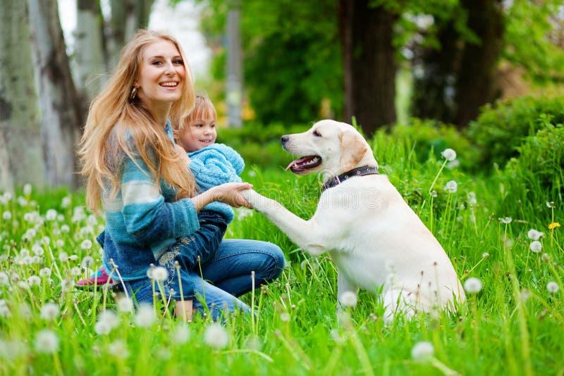 Mujer con la muchacha y el perro fotos de archivo