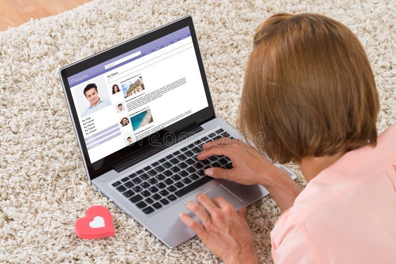 Mujer con la muestra del corazón que charla en sitio social del establecimiento de una red fotos de archivo libres de regalías